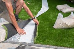 El jardinero profesional está cortando césped artificial para caber fotografía de archivo