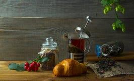 El jarro caliente del té en un fondo de madera rodeado por otoño da fruto Imagenes de archivo