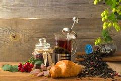 El jarro caliente del té en un fondo de madera rodeado por otoño da fruto Foto de archivo libre de regalías