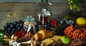 El jarro caliente del té en un fondo de madera rodeado por otoño da fruto Imagen de archivo