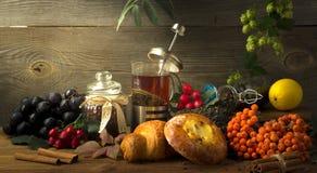 El jarro caliente del té en un fondo de madera rodeado por otoño da fruto Fotos de archivo