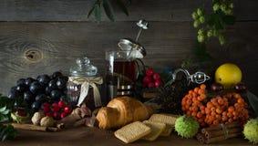 El jarro caliente del té en un fondo de madera rodeado por otoño da fruto Foto de archivo