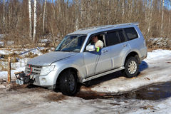 El jeep de las ruedas se pegó en cala en el camino forestal del hielo Fotos de archivo libres de regalías