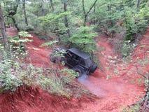 El jeep negro intenta subir una colina grande del camino Foto de archivo