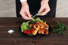 El jefe adornó el pollo picante en la tabla de madera Foto de archivo libre de regalías