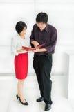 El jefe (asiático) tailandés está pidiendo una tarea para su secretaria en de Imagenes de archivo