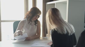 El jefe da a la mujer para firmar el contrato de empleo al emplear almacen de video