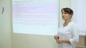 El jefe de la clínica médica conduce una conferencia en el departamento del hospital con el personal del hospital almacen de video