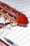 El jefe de la guitarra clásica, de notas, de nuevas secuencias y de una pluma en una tabla de madera Foto de archivo