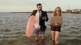 El jefe de vacaciones continúa dando órdenes a su secretaria en el medio del mar almacen de metraje de vídeo