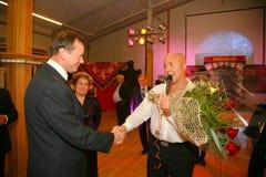 El jefe del doroshuk de Sergey del distrito de Priozersk que presenta las flores de los admiradores del cantante bielorruso Alexa Imágenes de archivo libres de regalías