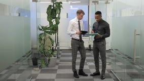 El jefe discute el informe con el encargado que se coloca en el pasillo de la oficina moderna almacen de metraje de vídeo
