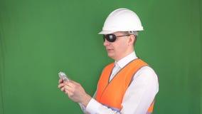 El jefe en un casco de la construcción y un chaleco de la señal cuenta de nuevo dólares del dinero después de una transacción ace almacen de video
