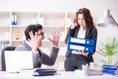 El jefe enojado infeliz con funcionamiento femenino del empleado imagen de archivo