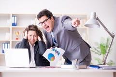 El jefe enojado infeliz con funcionamiento femenino del empleado fotografía de archivo libre de regalías