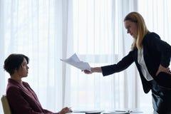 El jefe enojado regaña reprimenda de la mujer de negocios del empleado imagenes de archivo