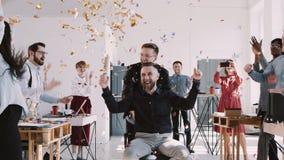 El jefe envejecido centro feliz ROJO de EPIC-W celebra éxito con el equipo y el confeti en la cámara lenta de la oficina sana mul almacen de video