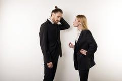 El jefe femenino en traje negro regaña a su encargado barbudo para no ser atento foto de archivo