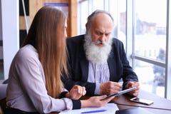 El jefe femenino joven discute al viejo empleado discute problemas en negocio imagenes de archivo