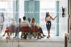 El jefe femenino muestra la presentación en la pantalla en la reunión de negocios imagen de archivo