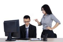 El jefe joven siente enojado a su empleado imagenes de archivo
