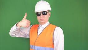 El jefe masculino en vidrios negros en un objeto de la construcción muestra que un gesto todo está bien, los pulgares para arriba almacen de video