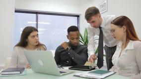 El jefe masculino explica la tarea a tres encargados en sitio de co-trabajo almacen de video