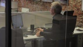 El jefe mayor funciona en el ordenador que se sienta en compañía próspera almacen de video