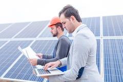 El jefe mira el ordenador portátil mientras que el trabajador mira el papel en las manos en el fondo de los paneles solares Fotos de archivo