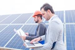 El jefe mira el ordenador portátil mientras que el trabajador mira el papel en las manos en el fondo de los paneles solares Foto de archivo