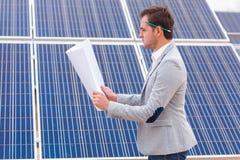 El jefe mira el proyecto en sus manos contra la perspectiva de los paneles solares Fotografía de archivo libre de regalías
