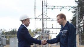 El jefe sacude las manos con el trabajador contra la perspectiva de la central eléctrica metrajes