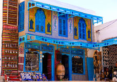 El Jem Gift Shop, Tunisian Blue Window Shutters, Traditional Arabic Art. Tradicional tunisian white building with beautiful blue window shutters, El Jem, Tunisia Stock Images
