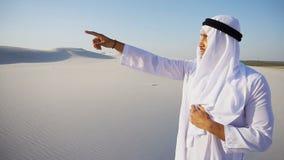 El jeque hermoso del emirato mira hacia fuera en la caravana de la distancia de camellos imagen de archivo