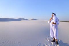 El jeque hermoso del emirato mira hacia fuera en la caravana de la distancia de camellos Fotos de archivo libres de regalías