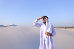 El jeque hermoso del emirato mira hacia fuera en la caravana de la distancia de camellos Imagen de archivo libre de regalías
