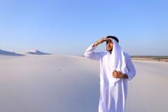 El jeque hermoso del emirato mira hacia fuera en la caravana de la distancia de camellos Fotografía de archivo libre de regalías