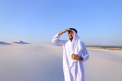 El jeque hermoso del emirato mira hacia fuera en la caravana de la distancia de camellos Fotos de archivo