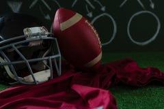 El jersey del fútbol americano, el engranaje principal y el fútbol mintiendo en césped artificial contra estrategia suben Foto de archivo