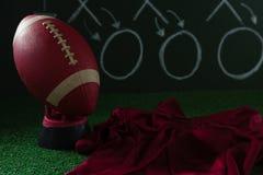 El jersey del fútbol americano y el fútbol que mienten en césped artificial contra estrategia suben Imagenes de archivo