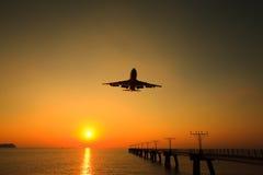 El jet del aire está aterrizando con la puesta del sol imagenes de archivo