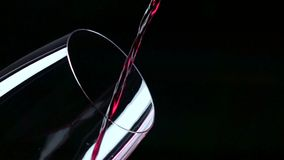 El jet del vino que es vertido en un vidrio, negro, primer, a cámara lenta almacen de metraje de vídeo