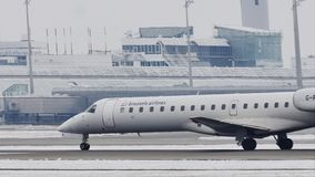 El jet regional de Bmi Embraer ERJ-145 G-RJXI aterrizó en el aeropuerto de Munich, MUC, nieve almacen de metraje de vídeo