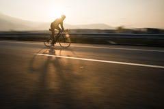 El jinete de la bicicleta monta rápidamente fotografía de archivo