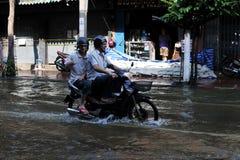El jinete de la moto navega una calle inundada Imagen de archivo