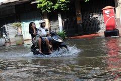 El jinete de la moto navega una calle inundada Fotos de archivo