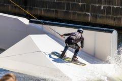 El jinete del estilo libre de Wakeboard hace los trucos en la competencia imagenes de archivo