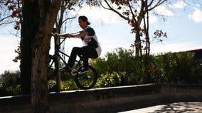El jinete lindo del bmx del hombre joven monta en calle en camino y saltos en encintado de la pared metrajes