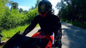 El jinete masculino conduce rápidamente en una moto almacen de metraje de vídeo