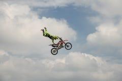 El jinete profesional del estilo libre realiza un truco con la motocicleta en el fondo del cielo azul de la nube Deporte extremo  Foto de archivo libre de regalías